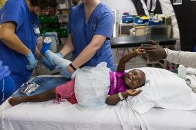 Stefanie Neeb, Rehab Team Leader, changes Cecilia's cast while she holds her father's hand.