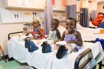 Three little orthopedic patients laugh and play on one of the ward beds.