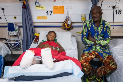 Justine in the ward on her first day out of surgery with her father by her side